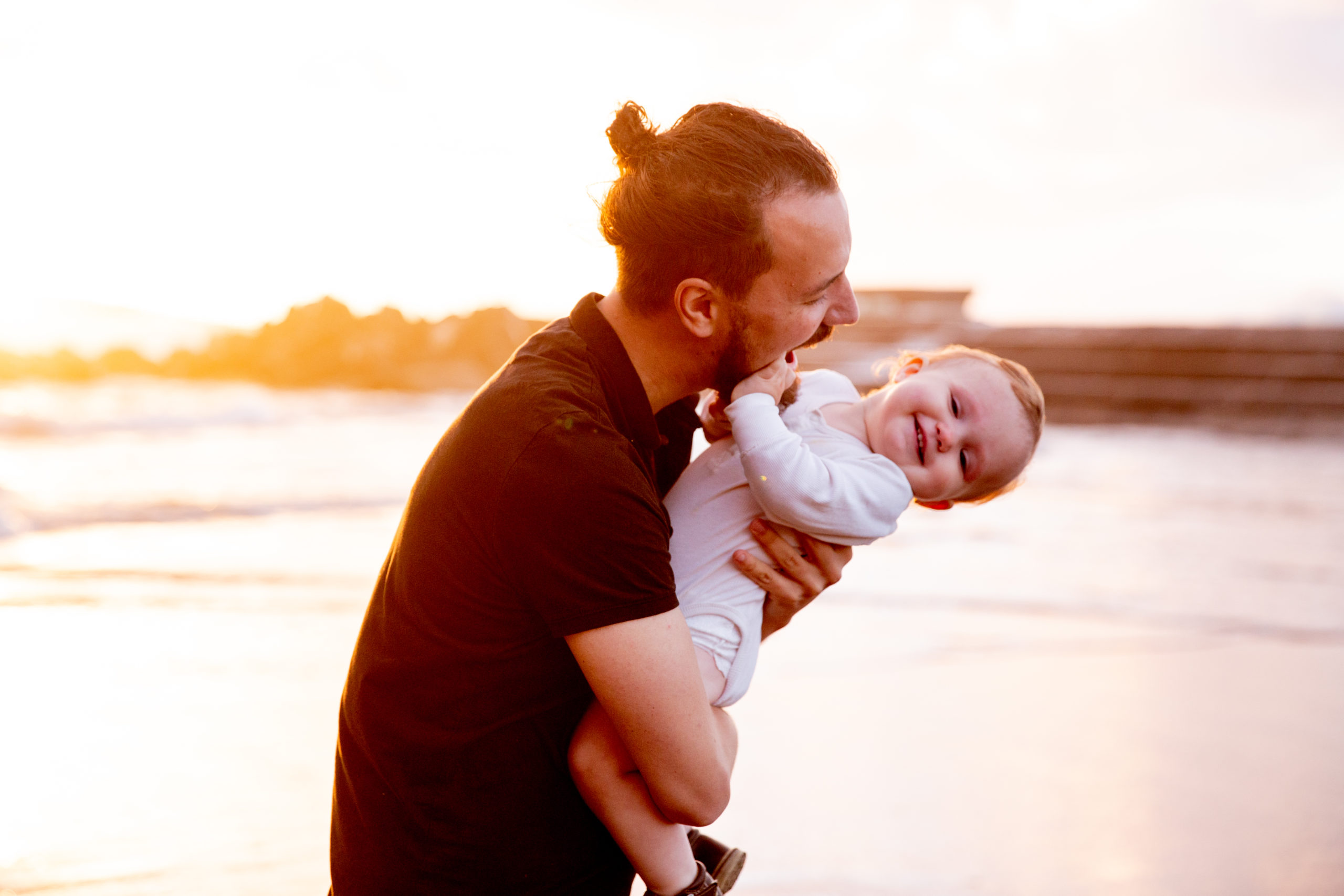 dad playing with child on the beach