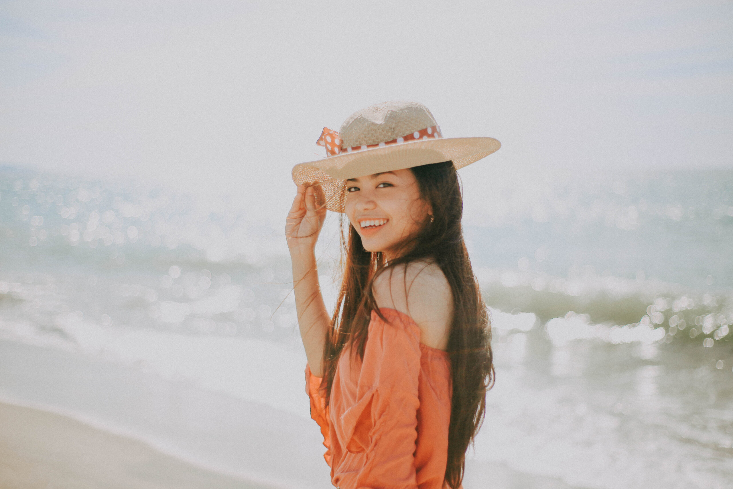 smiling girl at the beach with a hat on