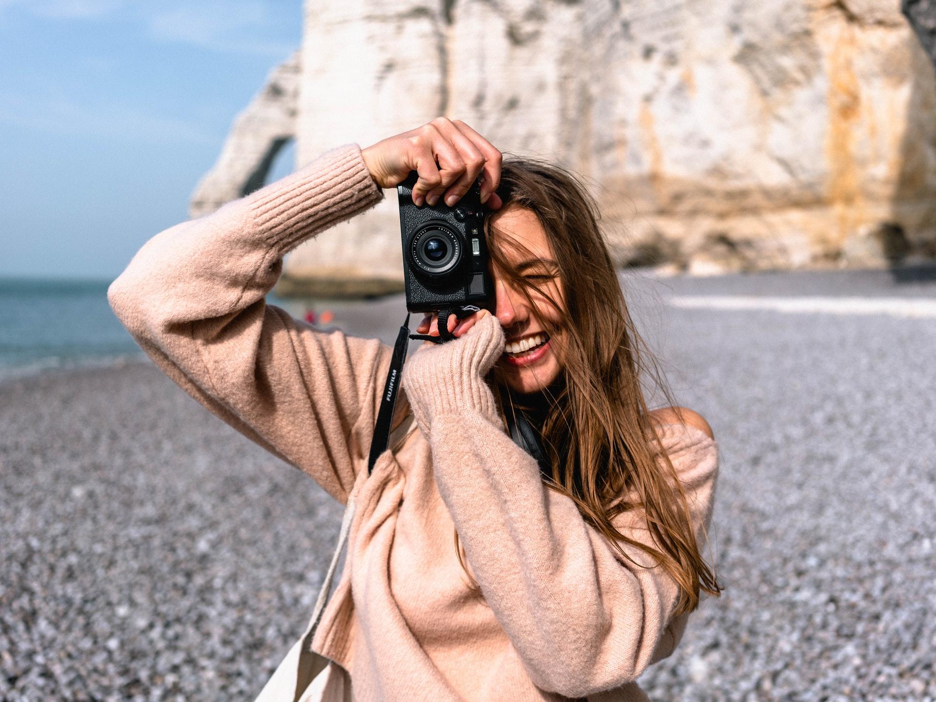smiling woman on la jolla beach holding camera